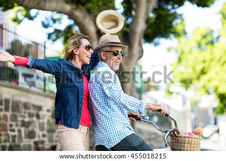 Happy couple enjoying while riding bicycle in city