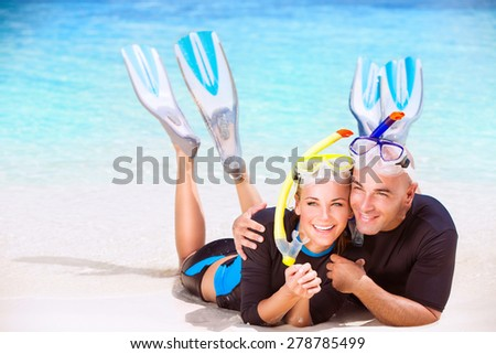 Happy couple enjoys beach activities, tourists lying down on sandy coast and hugging each other, wearing snorkeling gear, water sport, spending honeymoon vacation on beach resort - stock photo