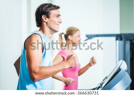 Happy couple exercising in gym