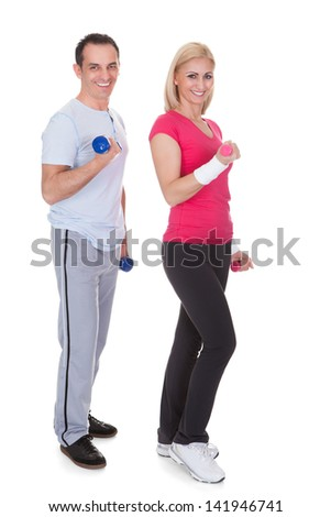 Happy Couple Exercising With Dumbbells Over White Background