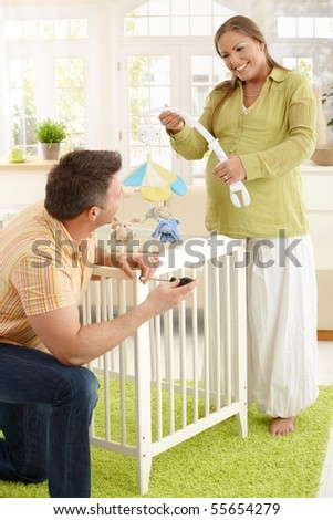 Happy couple expecting baby putting baby bed together in living room, laughing. - stock photo