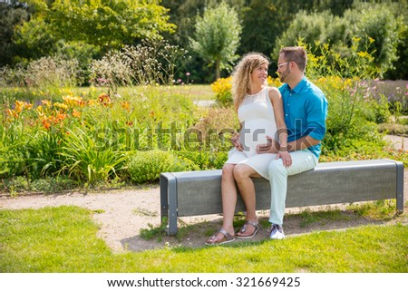 Happy couple expecting baby, sitting on bench in park - stock photo
