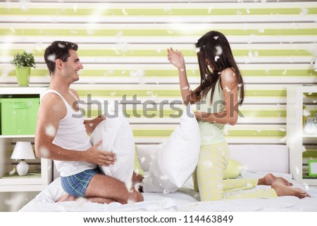 happy couple fighting with pillows in bed - stock photo