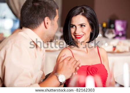 happy couple flirting at restaurant table - stock photo