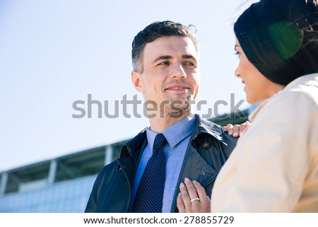 Happy couple flirting outdoors and looking to each other - stock photo