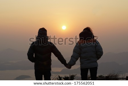 happy couple found each other , backlit scenes, first day hand in hand sunrise a new year honeymoon , hiking on the peak, seaview landscape with beautiful skyline in good morning background - stock photo