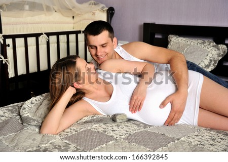 Happy couple future parents relaxing at home on a bed. - stock photo