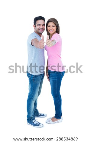 Happy couple gesturing thumbs up and looking at camera on white background - stock photo