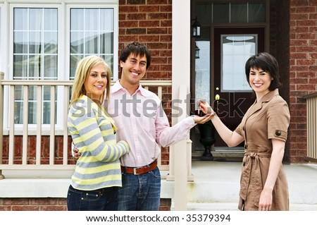 Happy couple getting keys to new house from real estate agent - stock photo