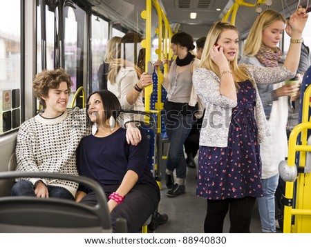 Happy couple going by bus with large group of people - stock photo