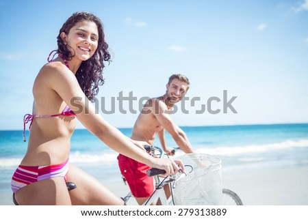 Happy couple going on a bike ride at the beach - stock photo