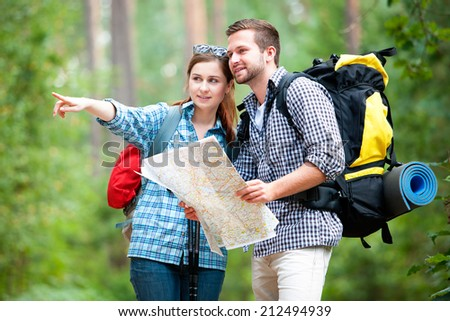 Happy couple going on a hike together in a forest - stock photo