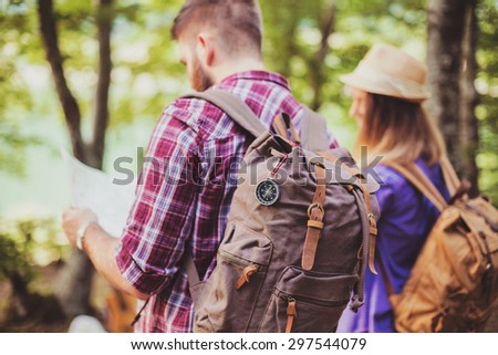 Happy couple going on a hike together in a forest looking in the map. Shallow depth of field - stock photo