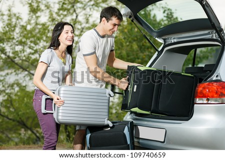 Happy couple going to vacations, loading their car boot with travel suitcases - stock photo
