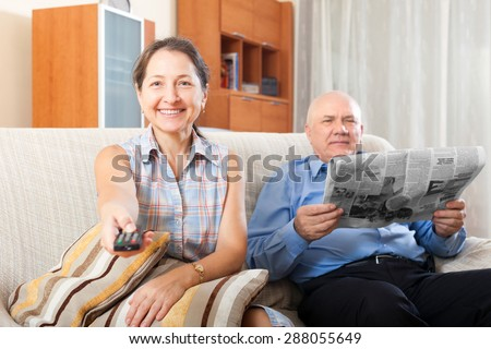 Happy couple grandparents reading a newspaper at home - stock photo
