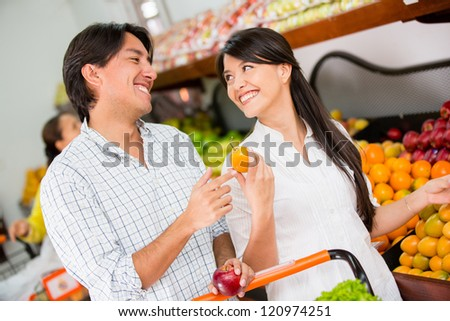 Happy couple grocery shopping at the local market