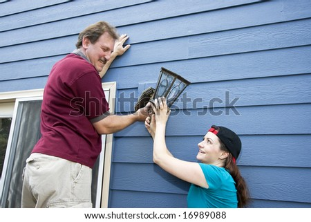 Happy couple hanging a light fixture on a house.Horizontally framed photo. - stock photo