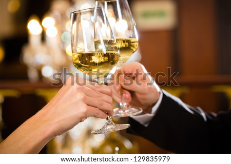 happy couple have a romantic date in a fine dining restaurant they drink wine and clinking glasses, cheers - closeup - stock photo
