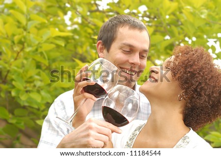 Happy couple having a fun time outside drinking and laughing - stock photo