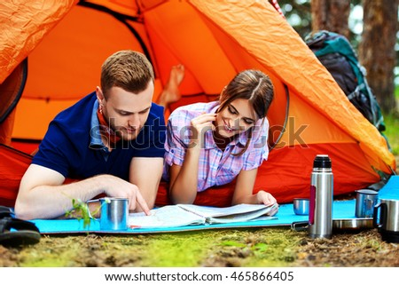 Happy couple having a rest in a camp tent. Hiking, camping.
