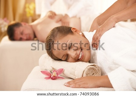 Happy couple having back massage in day spa. - stock photo
