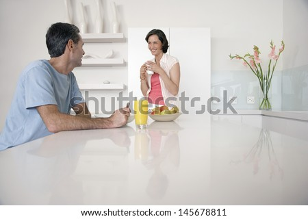 Happy couple having breakfast at kitchen bench - stock photo