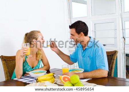 happy couple having breakfast together - stock photo