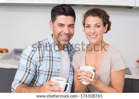 Happy couple having coffee smiling at camera at home in kitchen - stock photo