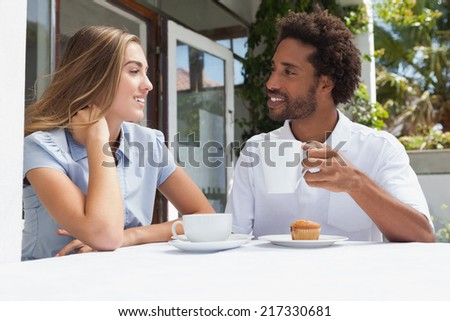 Happy couple having coffee together outside at the coffee shop