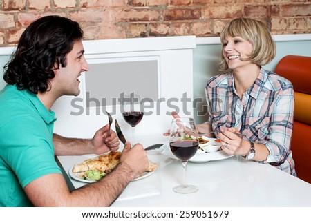 Happy couple having dinner at a restaurant - stock photo