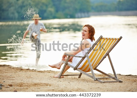 Happy couple having fun in summer on beach of a lake