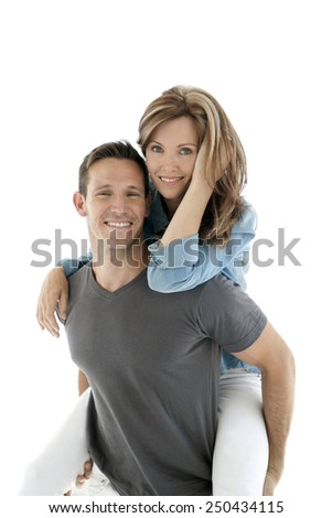 Happy couple having fun - man giving piggyback ride to woman - isolated - stock photo