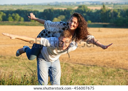 happy couple having fun on outdoor, girl riding on man back and fly - romantic travel and people concept, summer landscape with wheaten field - stock photo