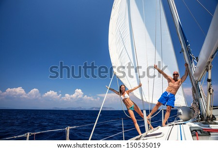 Happy couple having fun on sailboat, young family in water cruise, yachting sport, active lifestyle, summer vacation, romantic trip, travel and tourism concept  - stock photo