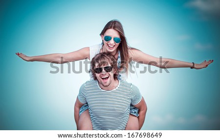 happy couple having fun on the beach , making plane with arms - stock photo
