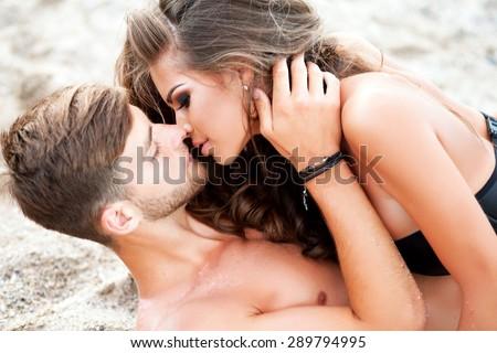 Happy Couple having fun on the Beach.Summer Vacation.Laughing Family enjoying Nature over Sea Background.Attractive Man and Woman at the Beach kissing each other,love on the beach,sensual people - stock photo