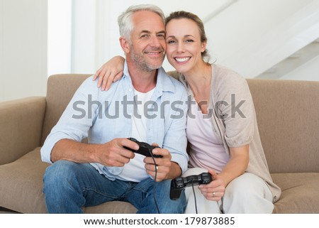 Happy couple having fun on the couch playing video games at home in the living room
