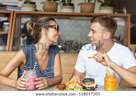 Happy couple having lively conversation on their first date, having joyful and carefree expressions, looking at each other and laughing. Man in white t-shirt sharing positive news with woman in shades