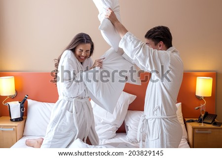 Happy Couple Having Pillow Fight in Hotel Room - stock photo