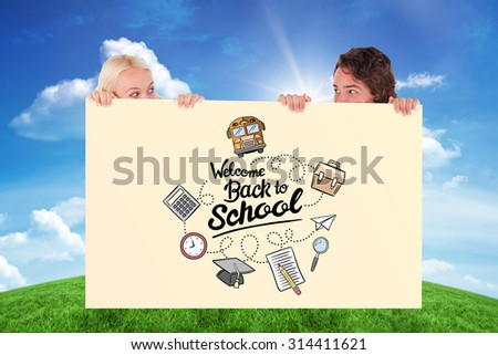 Happy couple hiding against green hill under blue sky - stock photo