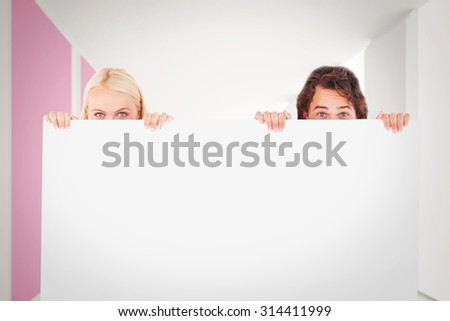 Happy Couple hiding behind a whiteboard against modern white and pink room with window - stock photo