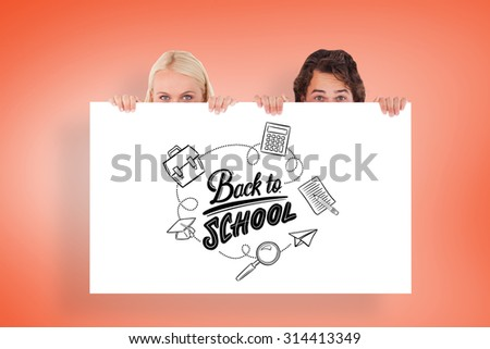 Happy Couple hiding behind a whiteboard against orange - stock photo
