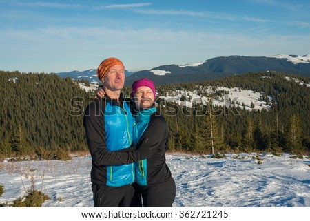 Happy couple hikers hugging and laughing during winter travel in the Carpathian mountains. Sunny winter day in mountains. - stock photo