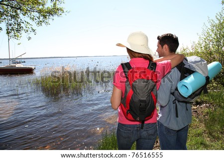Happy couple hiking by a lake - stock photo