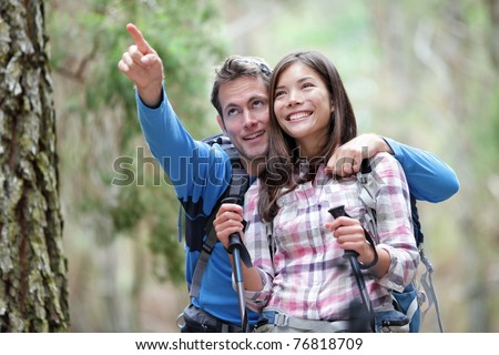 Happy couple hiking outdoors in forest. Active young asian woman hiker and caucasian man. - stock photo