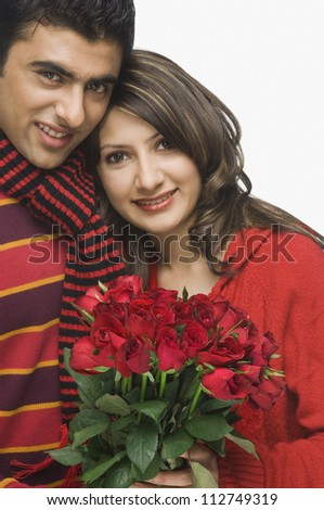 Happy couple holding a bouquet of roses