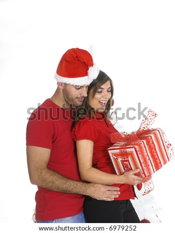 Happy couple holding a Christmas present near a white tree - stock photo