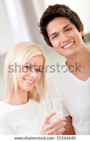 Happy couple holding a glass of milk and smiling - indoors