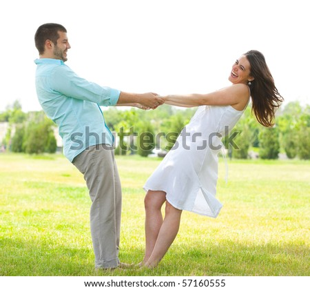 Happy couple holding arms outdoors - stock photo