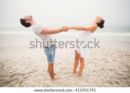 Happy couple holding hands and bending backwards on the beach - stock photo